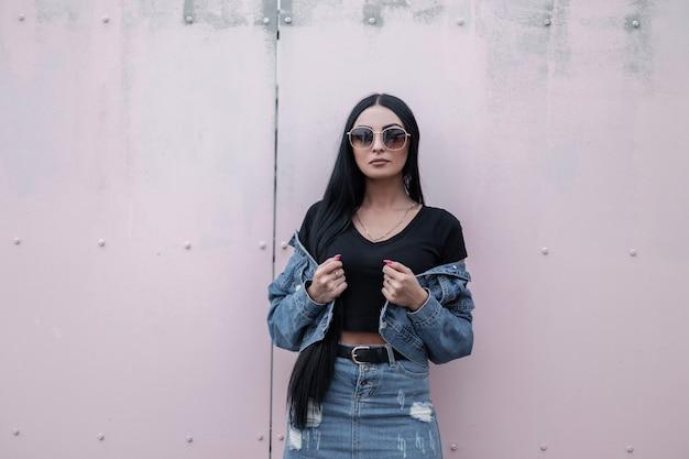 Moderne belle jeune femme hipster dans des lunettes de soleil noires élégantes se dresse et redresse une veste de mode en denim près d'un mur vintage. modèle de jolie fille brune dans des vêtements à la mode posant à l'extérieur.