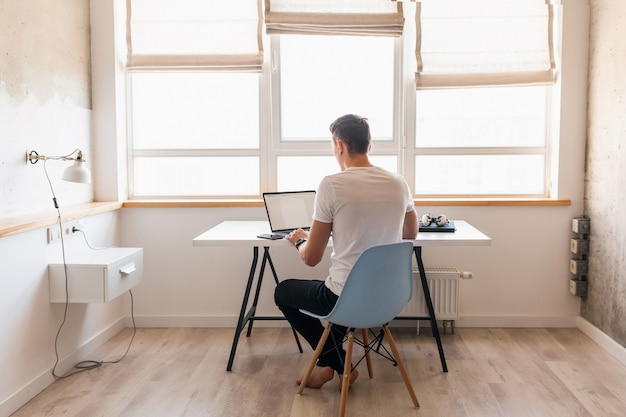 Moderne jeune bel homme en tenue décontractée assis à table travaillant sur ordinateur portable, pigiste à la maison