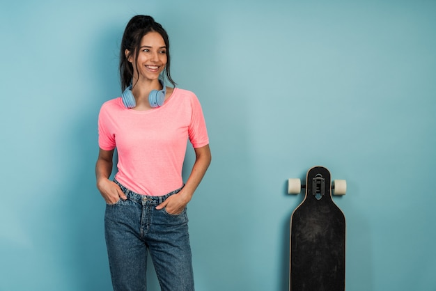 Moderne, jeune fille aux cheveux noirs, portant des écouteurs posant avec une planche à roulettes