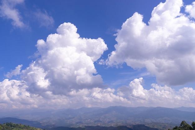 Moelleux nuage blanc dramatique sur un ciel bleu sur la montagne verte