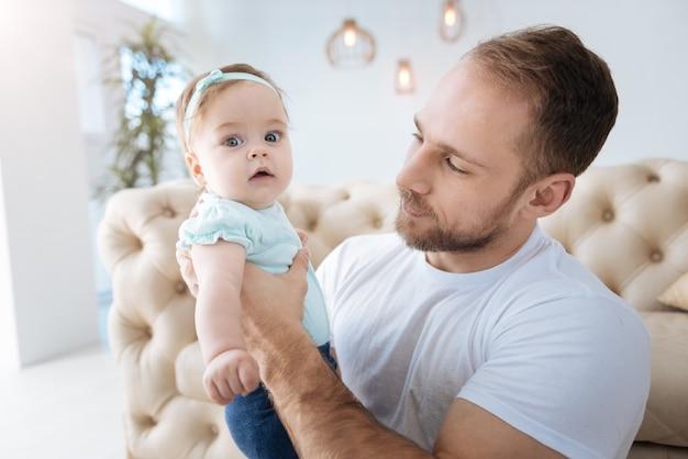 Moi et mon père. drôle belle fille agréable debout près de son jeune père et regardant ailleurs tout en exprimant son intérêt et sa positivité