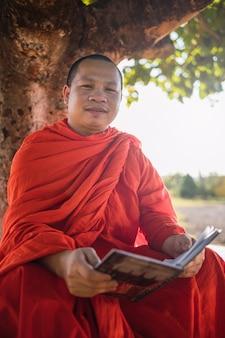 Moine bouddhiste lisant à l'extérieur.