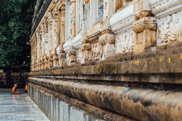 Moine bouddhiste en méditation sous l'arbre bodhi dans la région du temple mahabodhi alors qu'il pleuvait à bodh gaya