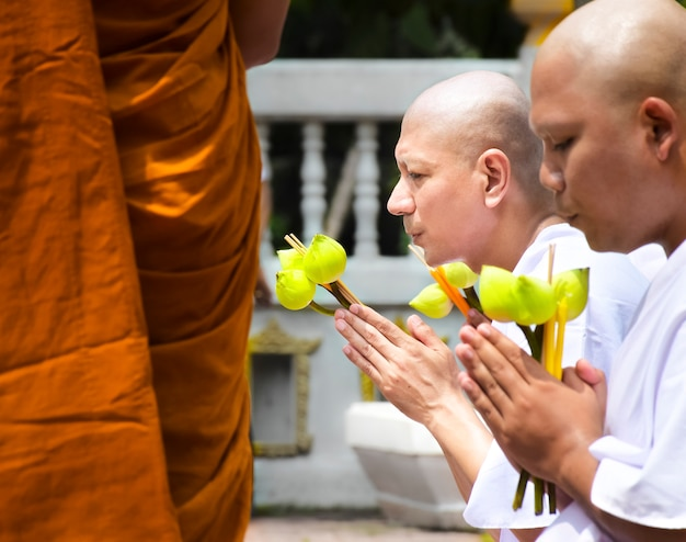 Un moine bouddhiste nouvellement ordonné prie avec un prêtre