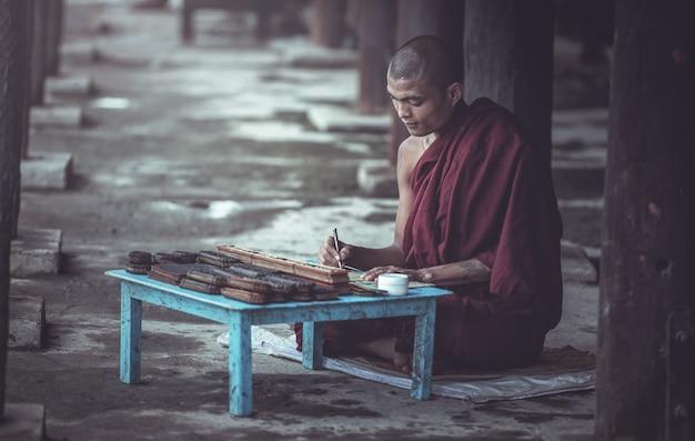 Un moine étudie dans un temple en lisant un livre, temple d'état shan au myanmar