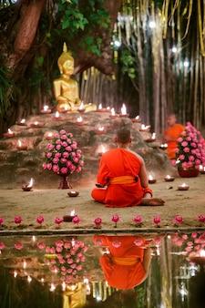 Des moines assis méditent avec de nombreuses bougies dans un temple thaïlandais la nuit