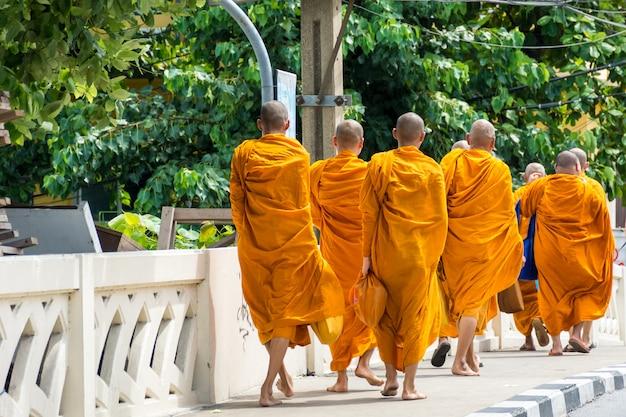 Des moines marchent dans la rue.