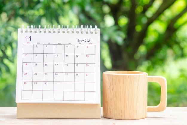 Mois de novembre, bureau du calendrier 2021 pour l'organisateur à la planification et rappel sur table en bois avec fond de nature verte.
