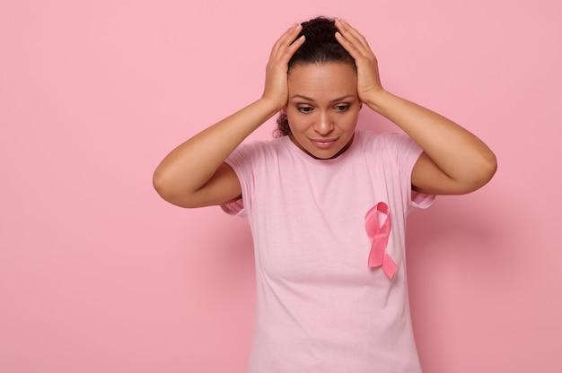 Mois de sensibilisation au cancer du sein d'octobre, femme en t-shirt rose avec ruban rose pour soutenir les personnes vivant et malades, se tenant la main sur la tête, isolée sur fond rose avec espace de copie pour le texte