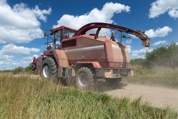 Moissonneuse rouge sur un champ rural, récolte du grain par une journée d'été ensoleillée, conduite le long de la route.