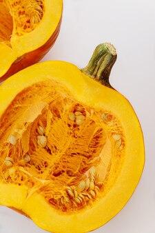 La moitié de la citrouille orange avec des graines sur fond blanc. vue de dessus.