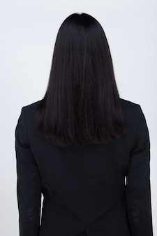 La moitié du corps portrait de femme asiatique cheveux raides noirs porter costume de bureau et tourner la vue arrière sur mur blanc isolé
