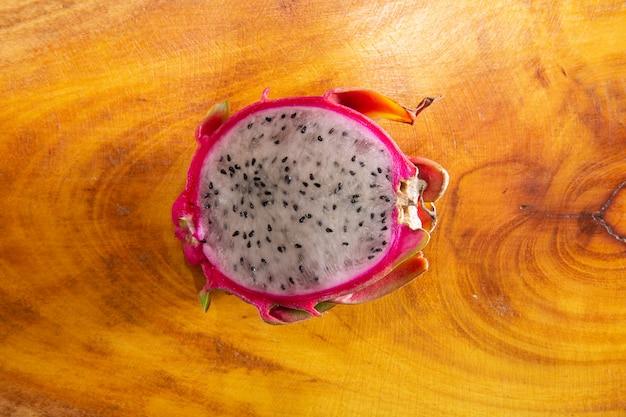 La moitié du fruit du dragon sur fond en bois rustique. pitaya ou fruit du dragon. fruits tropicaux exotiques.