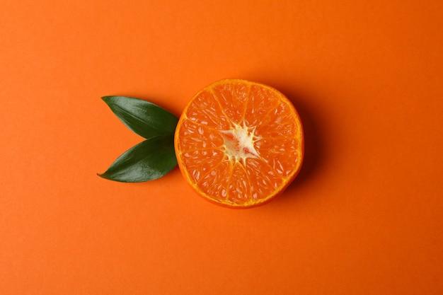 La moitié du mandarin avec des feuilles sur table orange
