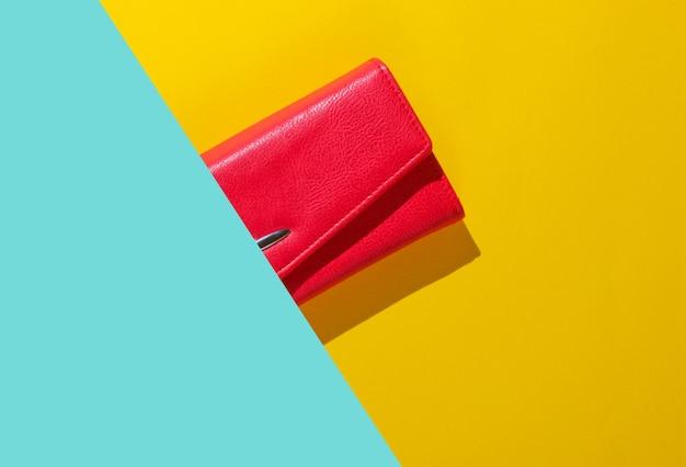 La moitié du portefeuille en cuir rouge sur fond jaune bleu. vue de dessus