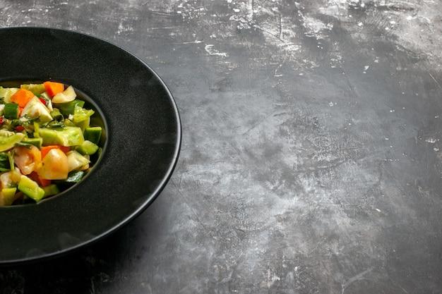 La moitié inférieure de la salade de tomates vertes sur une assiette ovale sur un espace libre sombre