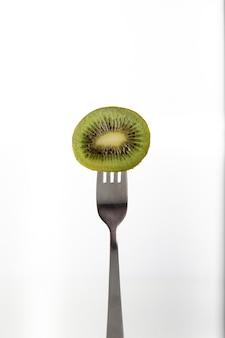 La moitié d'un kiwi percé sur une fourchette sur fond blanc