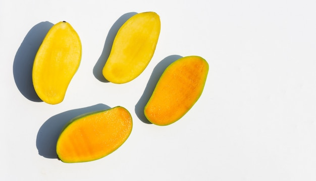 La moitié des mangues mûres coupées sur une surface blanche