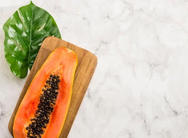 La moitié minimaliste de la papaye et de la feuille de monstera