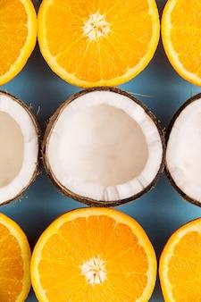 Une moitié de noix de coco blanche parmi les moitiés d'oranges juteuses