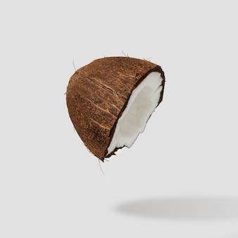 La moitié de la noix de coco craquelée sur une surface brillante.