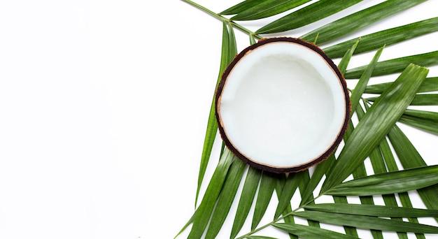 La moitié de la noix de coco sur les feuilles de palmiers tropicaux. vue de dessus