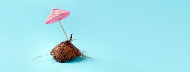 Moitié de noix de coco avec parapluie en papier