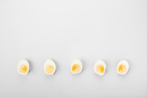 La moitié des œufs à la coque jaune et blanc sur fond gris.