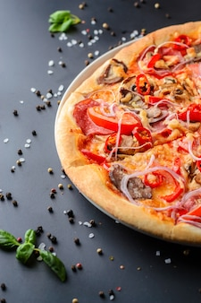 La moitié de la pizza italienne et des feuilles de basilic frais