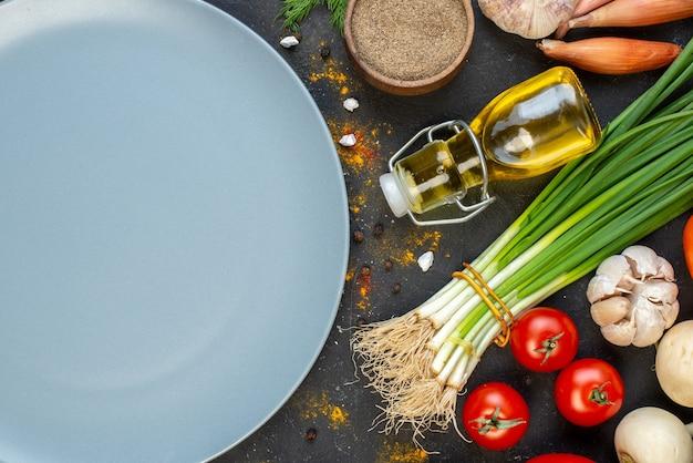 La moitié supérieure de l'assiette ronde grise des légumes frais et d'autres aliments sur l'obscurité