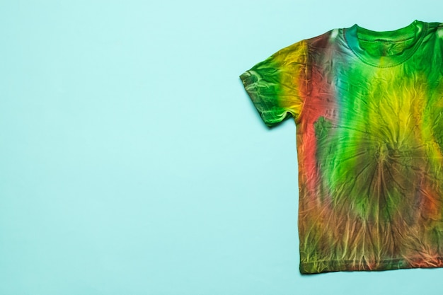 La moitié d'un t-shirt de style tie-dye sur fond bleu clair. espace pour le texte. coloration des vêtements à la main à la maison. mise à plat.
