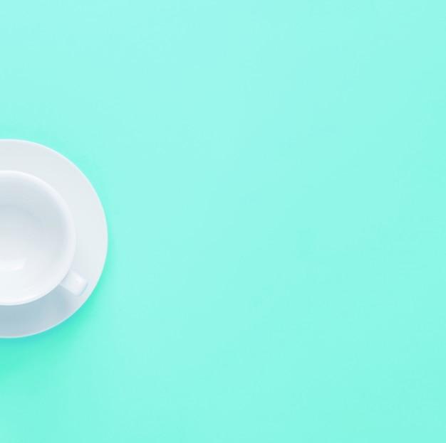 La moitié de tasse de thé ou de café vide blanche avec soucoupe sur fond turquoise.