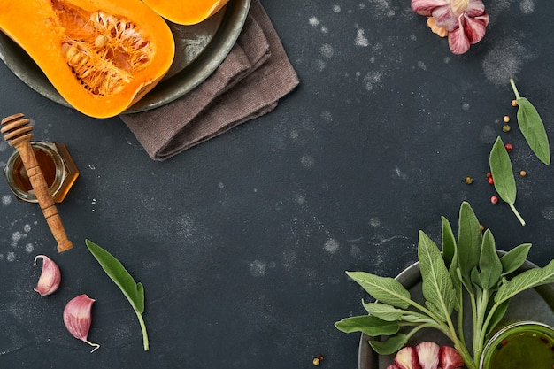Moitiés de courge musquée biologique crue avec feuille de sauge, ail au poivre multicolore, miel, sel et poivre sur fond d'ardoise noire, de pierre ou de béton. fond de nourriture. vue de dessus avec espace de copie.