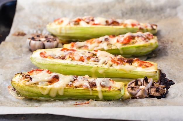 Moitiés de courgettes cuites au four prêtes à manger farcies de fromage et de tomates sur du papier sulfurisé sur une plaque à pâtisserie. plats de légumes, alimentation saine. fermer