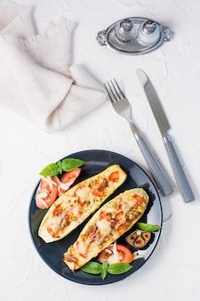 Moitiés de courgettes cuites au four prêtes à manger remplies de fromage et de feuilles de tomates et de basilic et de couverts sur une plaque noire sur un tableau blanc. menu de légumes, alimentation saine. vue de dessus et verticale
