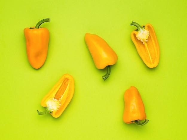 Moitiés et fruits entiers de poivre bulgare sur fond vert. la nourriture végétarienne.