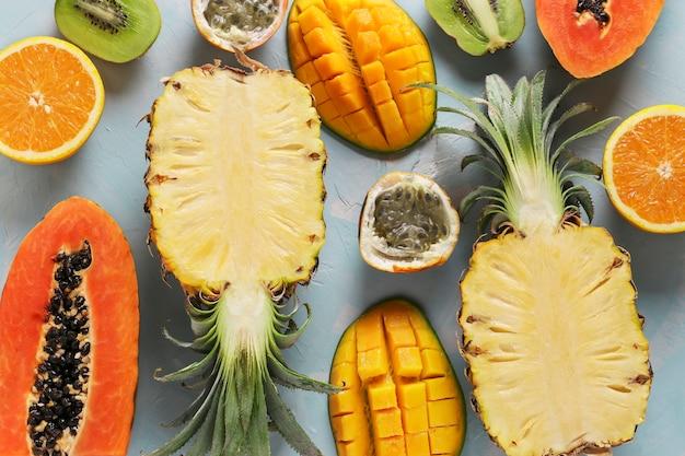 Moitiés de fruits tropicaux papaye, mangue, ananas, kiwi, orange et fruit de la passion sur fond bleu clair, vue de dessus