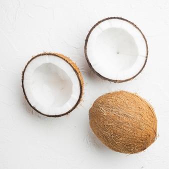 Moitiés de noix de coco, ensemble de morceaux de noix de coco, sur une table en pierre blanche