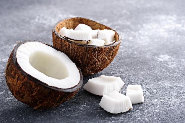 Moitiés de noix de coco sur fond gris avec espace copie