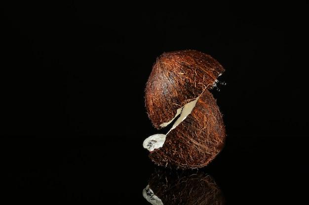 Moitiés de noix de coco mûre et éclaboussure d'eau sur l'obscurité