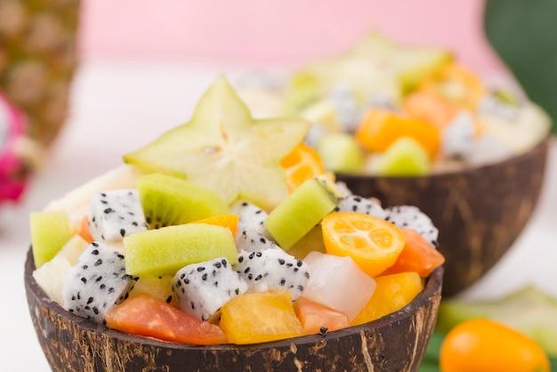Des moitiés de noix de coco remplies d'une délicieuse salade de fruits