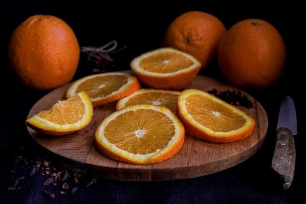 Des moitiés et des oranges entières sur une planche de bois sur fond noir, gros plan