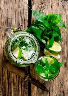 Mojito . cocktail cuit de citron vert, menthe, rhum et glace sur table en bois. vue de dessus