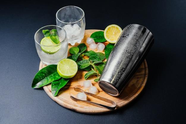 Mojito cocktail. menthe, citron vert, citron, glace et ustensiles de bar.