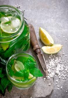 Mojito . cocktail en pot - feuilles de menthe, glace, rhum et citron vert sur une base en pierre avec un couteau pour les agrumes et le sucre.