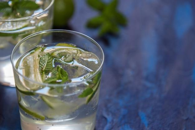Mojito cocktail avec ses ingrédients sur une table bleue