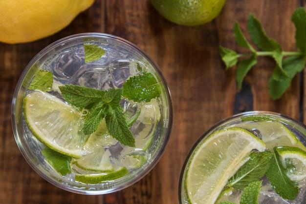 Mojito cocktail avec ses ingrédients sur une table en bois
