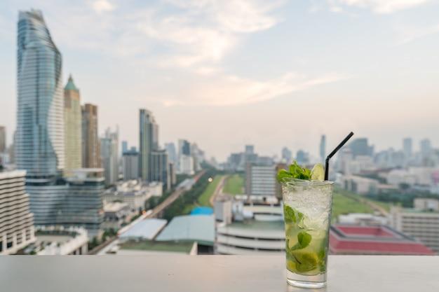 Mojito cocktail sur la table dans le bar sur le toit avec le point de vue sur la ville de bangkok à bangkok en thaïlande.