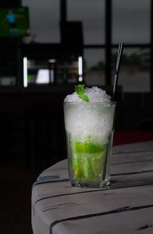Mojito long drink décoré de citron vert et de menthe avec de la glace pilée. dans un gobelet en verre collins. sur un fond en bois gris. fermer. lumière forte