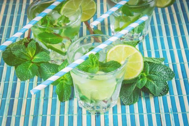 Mojito à la menthe et citron vert dans un verre et une carafe sur une serviette en bambou blanche et bleue.